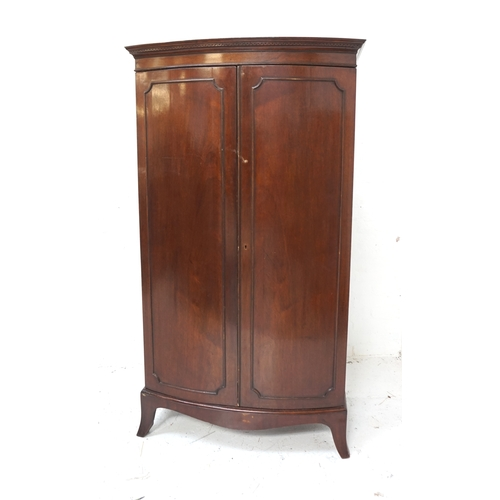 509 - MAHOGANY BOW FRONT WARDROBE with a moulded pediment above a pair of panelled doors opening to reveal...