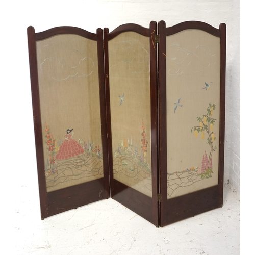 512 - EARLY 20th CENTURY MAHOGANY THREE FOLD SCREEN with arched panels above needlework panels depicting a...