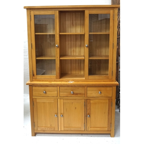 531 - MODERN LIGHT OAK SIDE CABINET with a moulded top above two adjustable shelves flanked by two glass c...