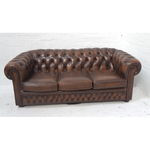 506 - CHESTERFIELD THREE SEAT SOFA in brown leather with a button back and arms with decorative stud detai...