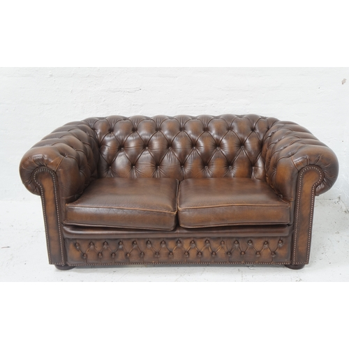 505 - CHESTERFIELD TWO SEAT SOFA in brown leather with a button back and arms with decorative stud detail,...
