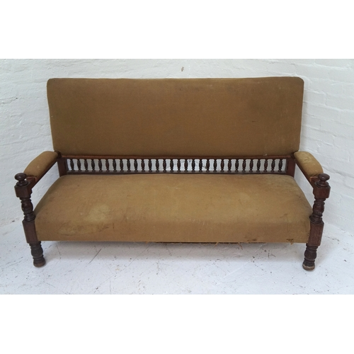 516 - IN THE MANNER OF LIBERTY'S OF LONDON an Aesthetic movement mahogany framed sofa with a padded back, ...