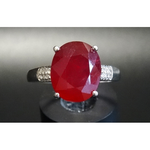 26 - RUBY AND DIAMOND RING the central oval cut ruby approximately 3.5cts flanked by six small diamonds t...
