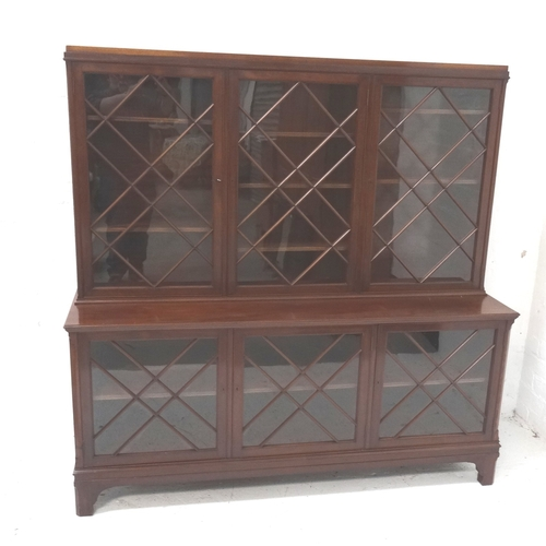 567 - MAHOGANY LIBRARY BOOKCASE with a moulded top above three lattice glazed doors flanked by canted side...