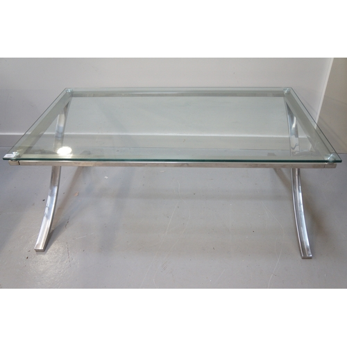553 - MODERN GLASS TOP OCCASIONAL TABLE with an oblong top on a polished steel base with X frame supports,...