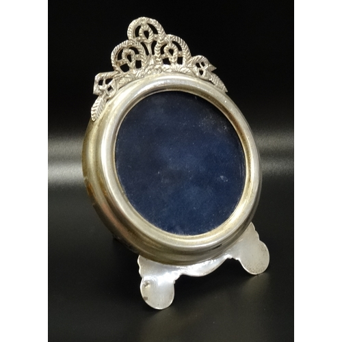 111 - SILVER PHOTOGRAPH FRAME the circular frame below a decorative pierced top section, on easel support,...