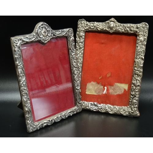 113 - AN EDWARDIAN AND A VICTORIAN SILVER PHOTOGRAPH FRAME both with profuse embossed scroll decoration, o...