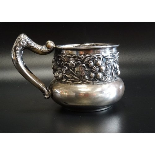 116 - EARLY 20th CENTURY AMERICAN EMBOSSED SILVER MUG with a band of floral and scroll decoration and shap...