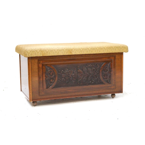 369 - TEAK BLANKET BOX with a lift up stuffover lid above a carved front panel, standing on later castors,...