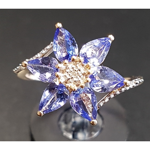 38 - ATTRACTIVE TANZANITE AND DIAMOND CLUSTER DRESS RING the central diamond surrounded by six pear cut t...