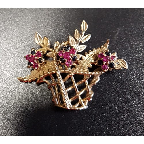 42 - RUBY AND SAPPHIRE NINE CARAT GOLD BROOCH  in the form of a basket of flowers, with three ruby and sa...