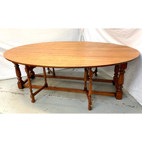375 - 20TH CENTURY CLOVER OAK WAKE TABLE with shaped drop flaps supported by double gatelegs to each side,...