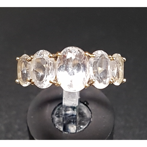 11 - GRADUATED CLEAR QUARTZ FIVE STONE RING on ten carat gold shank with decorative split shoulders, ring...