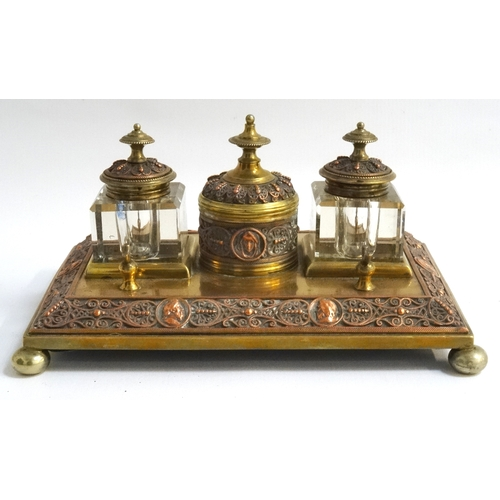 203 - COPPER AND BRASS DESK TOP INKWELL with opposing pen rests, two square glass inkwells flanking a circ...