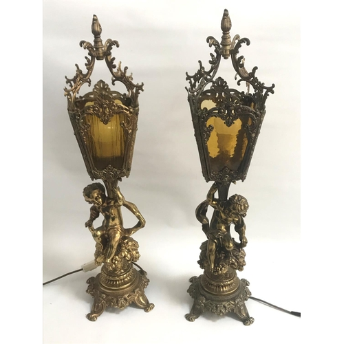 196 - LARGE PAIR OF GILT METAL LAMPS the columns with putti seated on bushes below four sided mottled yell...
