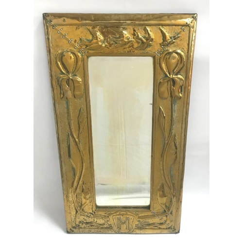352 - ARTS AND CRAFTS BRASS WALL MIRROR with an oblong embossed frame decorated with birds and flowers and...