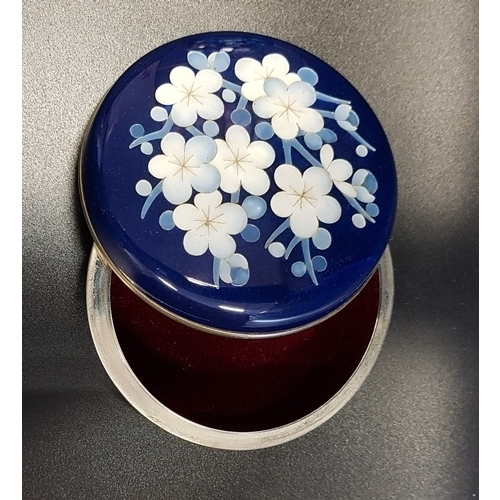 188 - JAPANESE ANDO CLOISONNE CIRCULAR TRINKET BOX with a dark blue ground, the lid decorated with flowers...