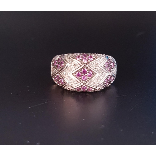 28 - DIAMOND AND PINK GEM SET BOMBE STYLE CLUSTER RING the gemstones in zigzag and rhombus shaped setting...