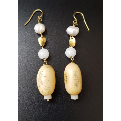 12 - UNUSUAL PAIR OF SCRIMSHAW AND PEARL DROP EARRINGS the scrimshaw bead on each with engraved figural a...
