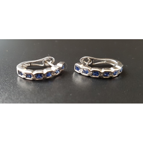 13 - PAIR OF SAPPHIRE HALF HOOP EARRINGS each earring set with six bezel set princess cut sapphires, in f...