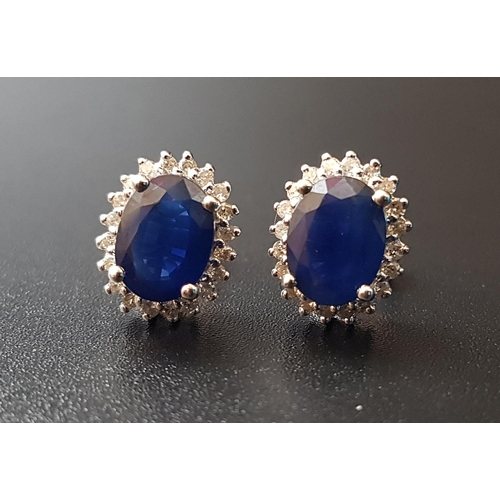 17 - PAIR OF SAPPHIRE AND DIAMOND CLUSTER STUD EARRINGS the central oval cut sapphire on each approximate...