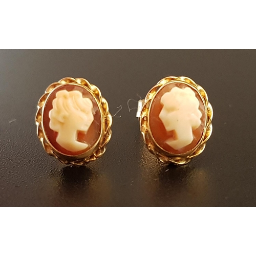 24 - PAIR OF SHELL CAMEO EARRINGS each with female bust in profile, in unmarked gold mounts, the butterfl...