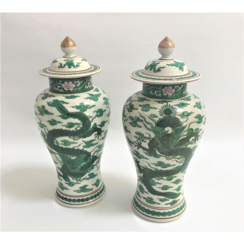 22 - PAIR OF CHINESE FAMILLE VERTE BALUSTER VASES  decorated with dragons and foliage, the circular lids ...