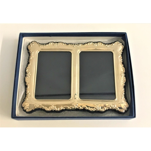 210 - SILVER DOUBLE PHOTOGRAPH FRAME with embossed floral decoration to the shaped edges, on easel support...
