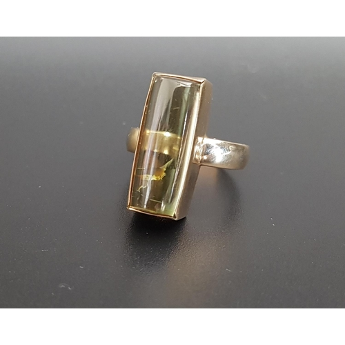 48 - UNUSUAL GREEN TOURMALINE DRESS RING  the domed rectangular gemstone approximately 2cm long, in nine ...