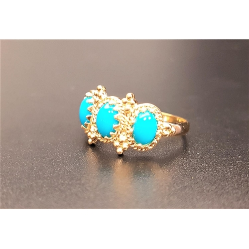 14 - TURQUOISE THREE STONE RING in decorative moulded setting, on nine carat gold shank, ring size N...