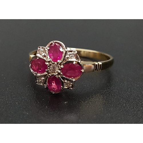 39 - RUBY AND DIAMOND CLUSTER RING the four oval cut rubies separated by small diamonds and with a furthe...