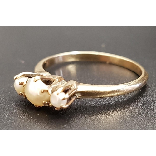 41 - GRADUATED PEARL THREE STONE RING on fourteen carat gold shank, ring size O and approximately 2.2 gra...