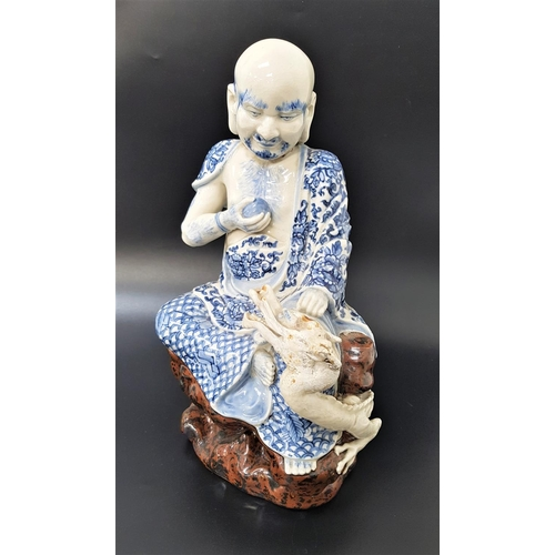 57 - CHINESE FIGURE ORNAMENT depicting a man holding a pearl seated beside a dragon, with blue and white ...
