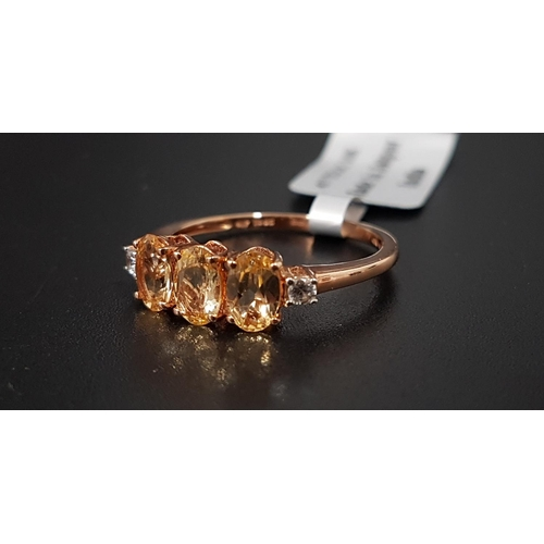 151 - CERTIFIED IMPERIAL OURO PRETO IMPERIAL TOPAZ AND WHITE ZIRCON RING the three oval cut topaz weighing...