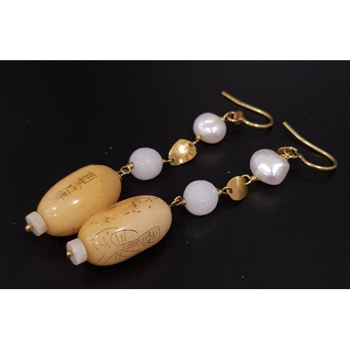 153 - UNUSUAL PAIR OF SCRIMSHAW AND PEARL DROP EARRINGS the scrimshaw bead on each with engraved figural a...