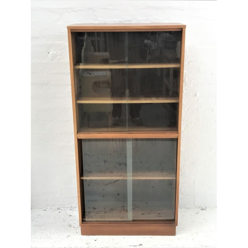 460 - TEAK BOOKCASE with a rectangular moulded top above a pair of sliding glass doors with two adjustable...