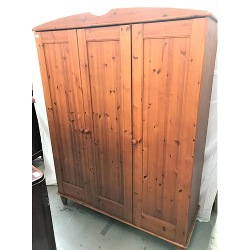 539 - WAXED PINE WARDROBE with a shaped pediment above three panelled doors opening to reveal shelves and ...