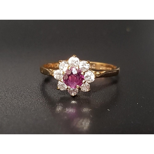 6 - RUBY AND CZ CLUSTER RING the round cut ruby surrounded by eight CZ stones, on nine carat gold shank,...