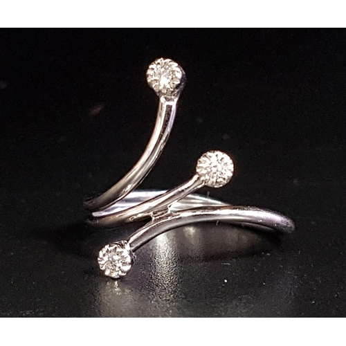 19 - ATTRACTIVE DIAMOND RING formed with three outswept arms, each terminating with a small diamond, in e...