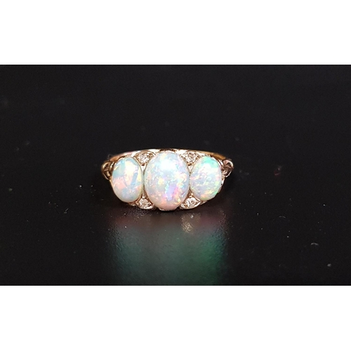 10 - PRETTY OPAL AND DIAMOND RING the three graduated oval cabochon opals with small diamonds between, on...
