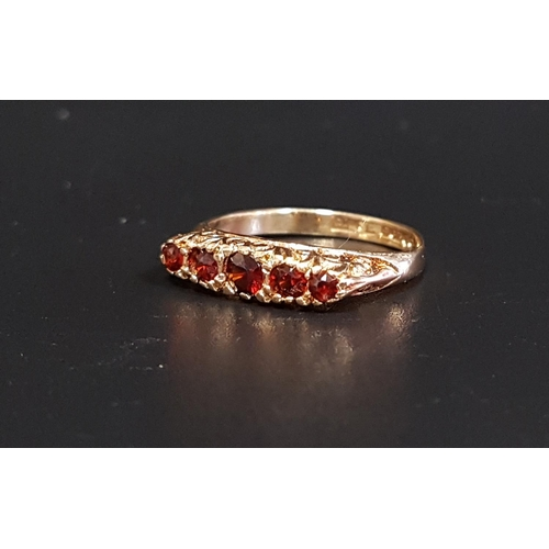 34 - GRADUATED GARNET FIVE STONE RING on nine carat gold shank with decorative pierced and scroll decorat...