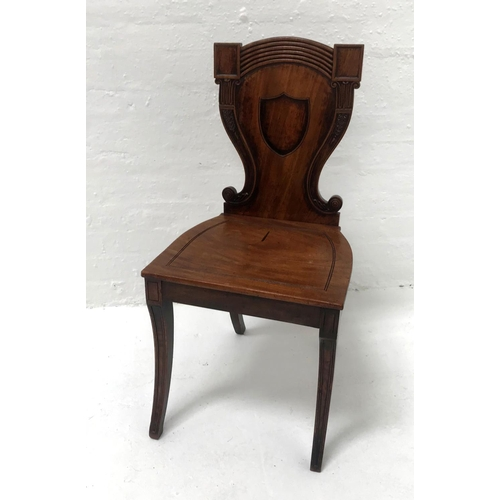 580 - 19th CENTURY MAHOGANY HALL CHAIR the carved shaped back centred with a shield, above a shaped solid ...