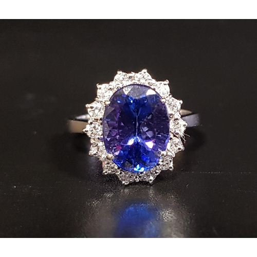 53 - IMPRESSIVE TANZANITE AND DIAMOND CLUSTER RING the large central oval cut tanzanite approximately 4.2...