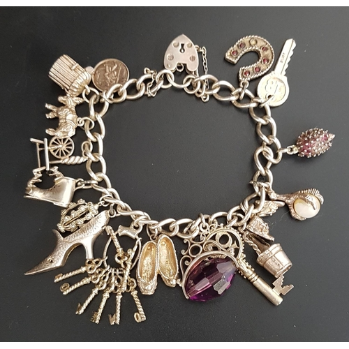 148 - SILVER CHARM BRACELET the curb link bracelet with silver heart padlock clasp and a good selection of...