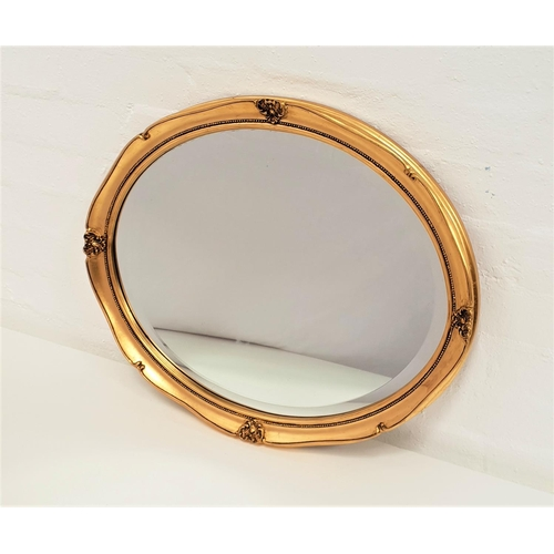 422 - OVAL GILTWOOD WALL MIRROR with an oval beveled plate, 56.5cm wide