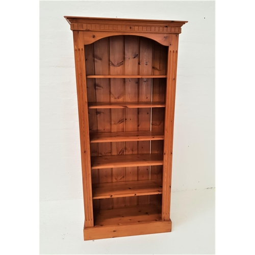 491 - WAXED PINE BOOKCASE with a moulded cornice above five shelves, standing on a plinth base, 197cm high