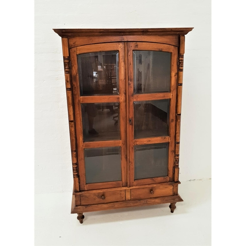 496 - TEAK CABINET with a moulded cornice above a pair of arched glass panel doors, opening to reveal shel...