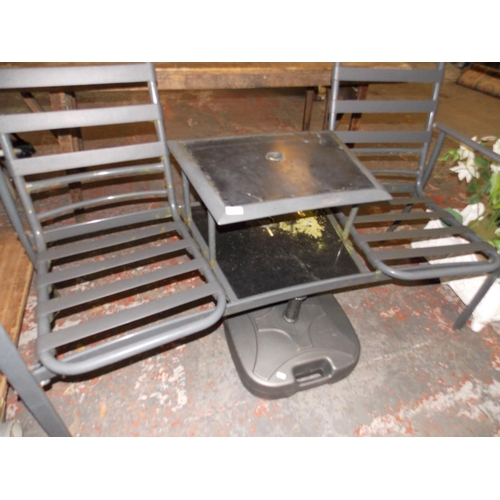 19 - A GREY METAL TWO SEAT GARDEN CHAIR WITH CENTRAL TABLE AND A PARASOL BASE...