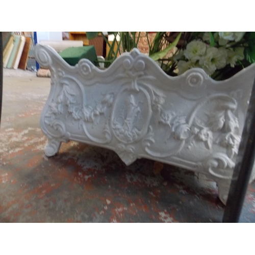 20 - A CAST IRON ORNATE WHITE PAINTED GARDEN PLANTER CONTAINING ARTIFICIAL FLOWERS...
