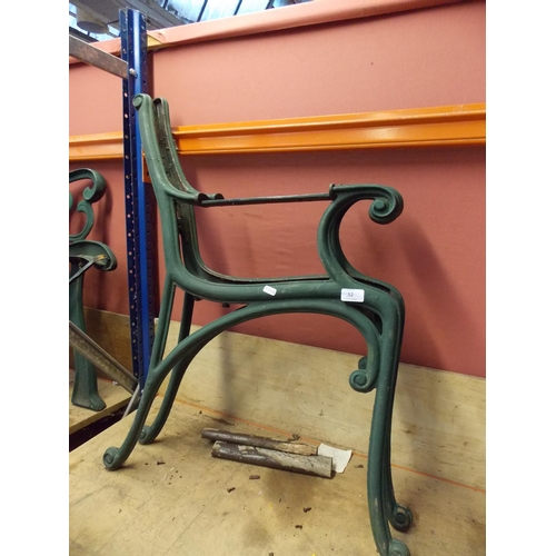 32 - A PAIR OF GREEN PAINTED CAST IRON ORNATE GARDEN BENCH ENDS...